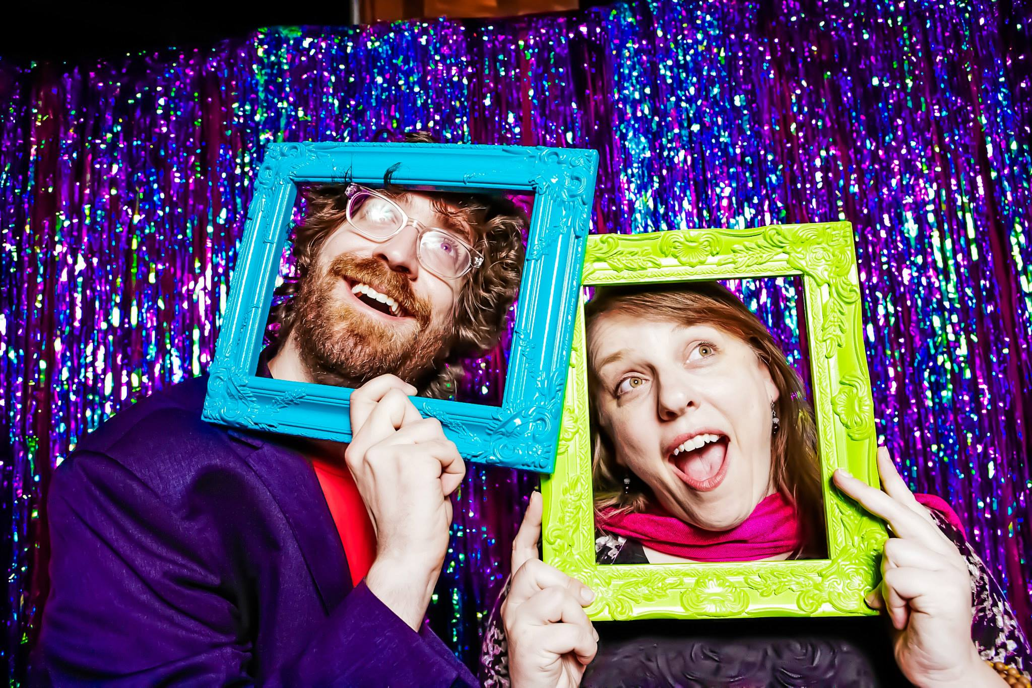 Christopher Schmitt and Ari Stiles standing next to each other in front of a glitter background, both with their heads sticking through bright blue and green picture frames, making faces.