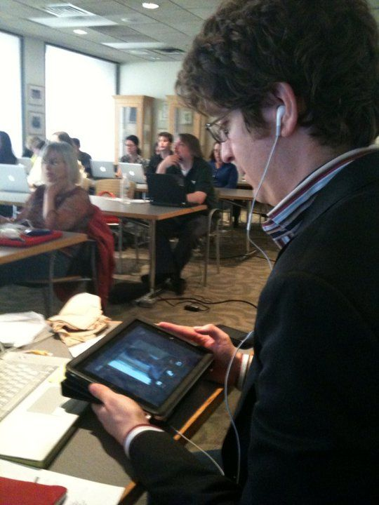 Christopher Schmitt watching a Summit event on an iPad