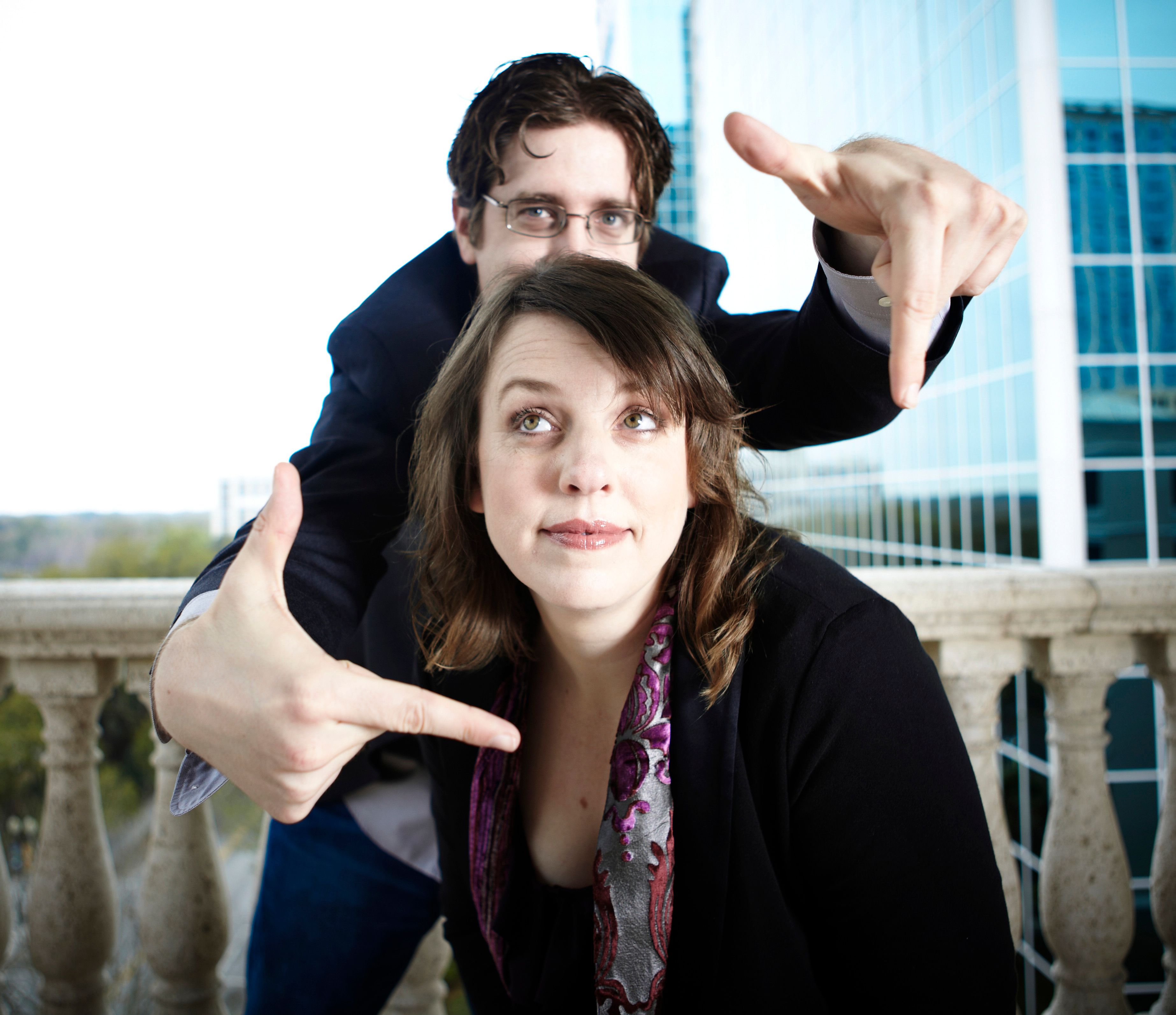 Christopher Schmitt and Ari Stiles, Christopher is standing behind Ari and frames her face with his extended thumb and index fingers.
