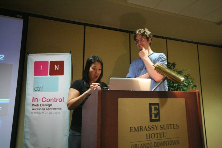 Christopher Schmitt smiling as Kelly Goto looks amazed at a phone at the 2010 Web Control Web Design Workshop Conference