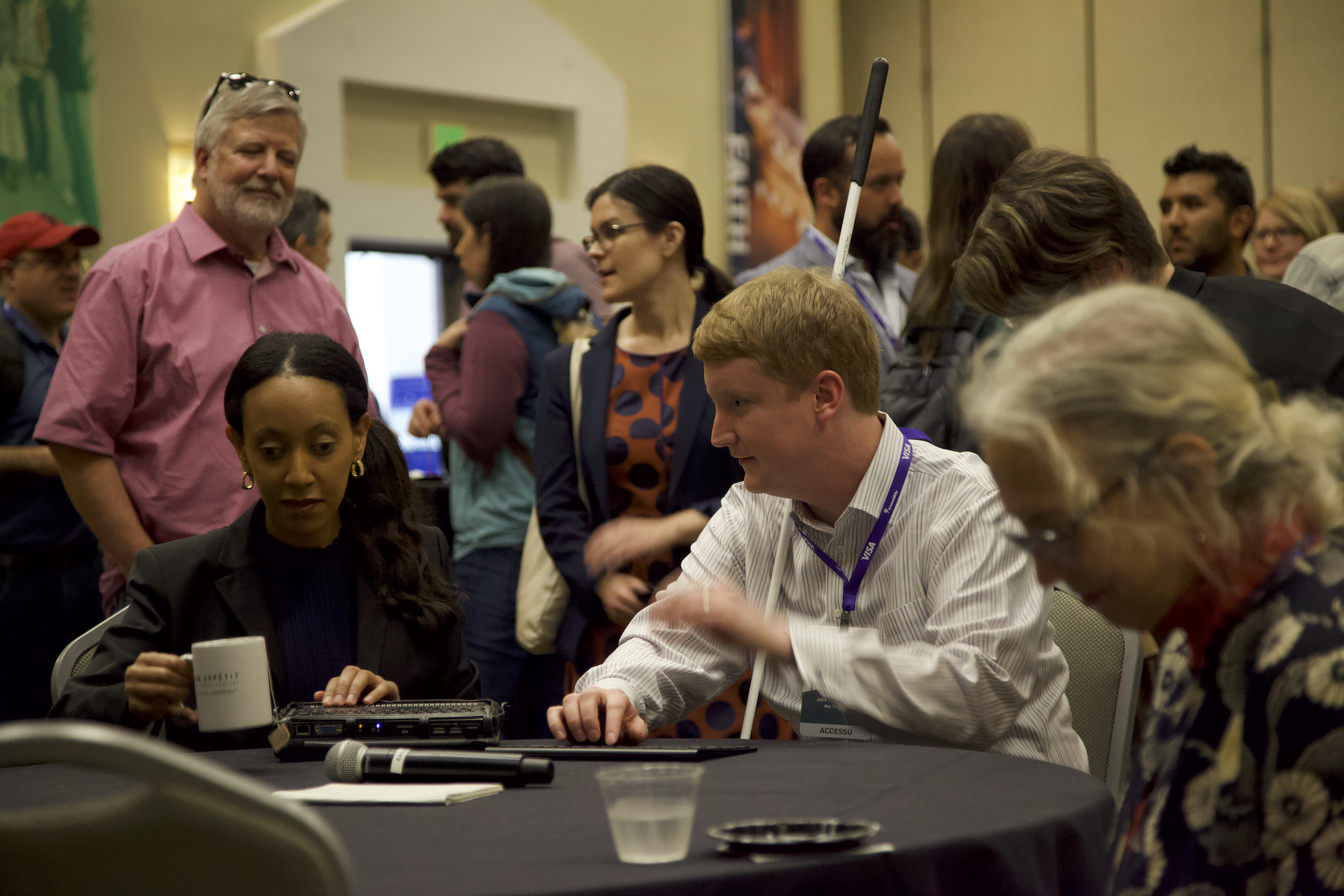 A man with a white cane and two women seated at a table in a crowded event hall at AccessU.