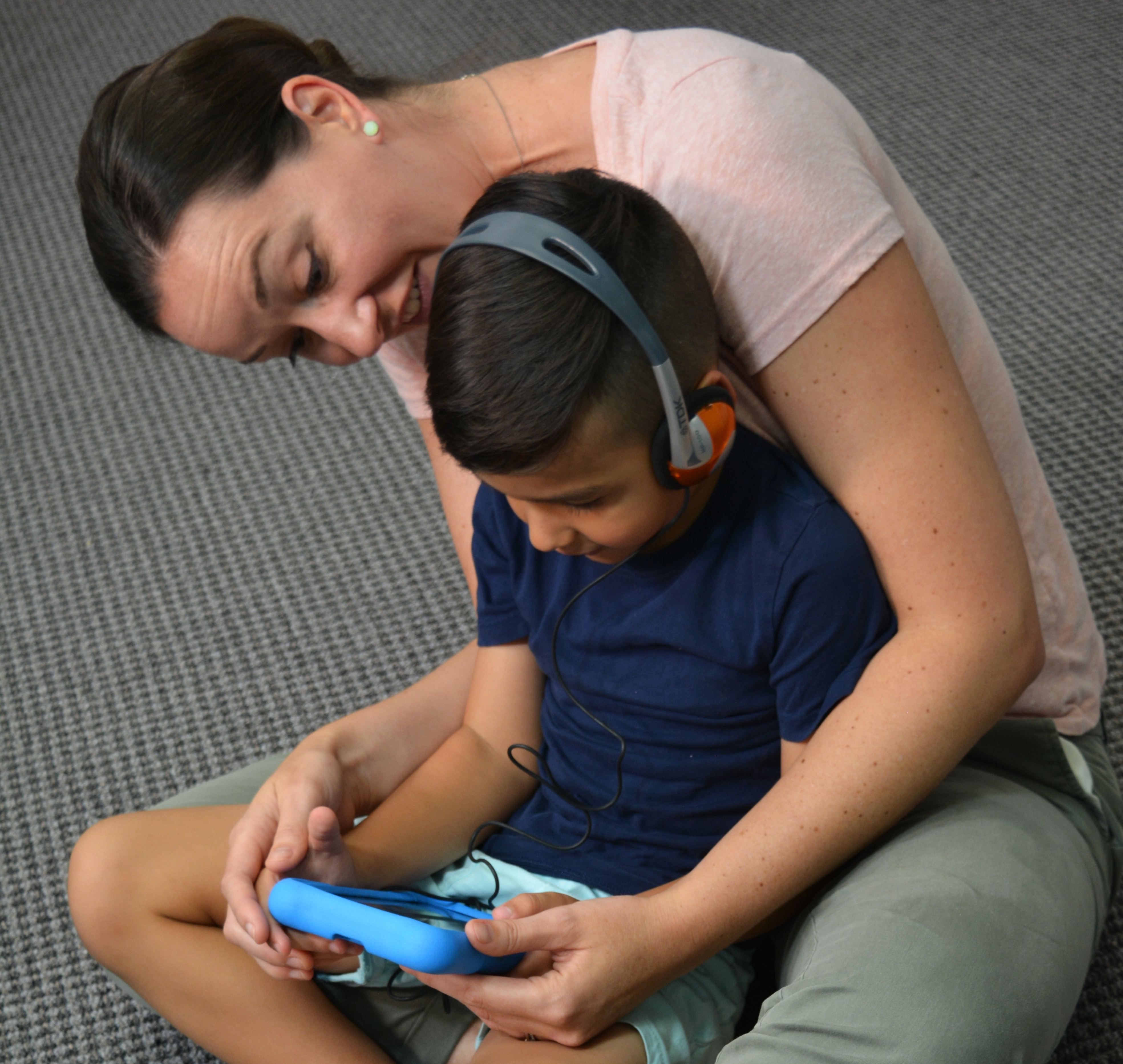 A boy using headphones and a tablet, seated in a woman's lap. She is looking at the tablet screen with him.